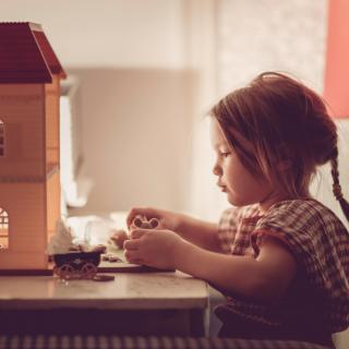 A small child plays with dollhouse furniture in front of a dollhouse.