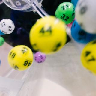 A large number of brightly-colored, numbered balls are caught spinning in a clear lottery tumbler.
