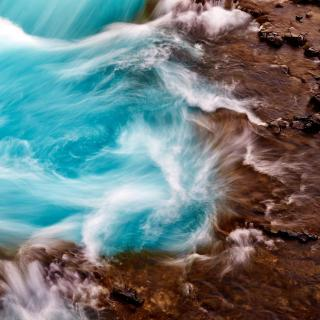 Ocean water swirls as it crashes against flat wet rocks.