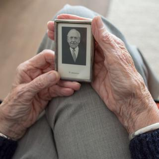 "Hands of an elder holding a photgraph with the words ""in memory"""