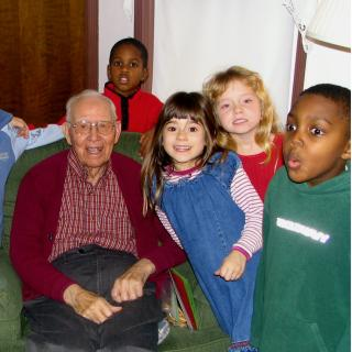 An elderly white man sits in a cozy green chair, smiling, surrounded by children around seven years old, two white girls and two black boys part of a larger group of kids.