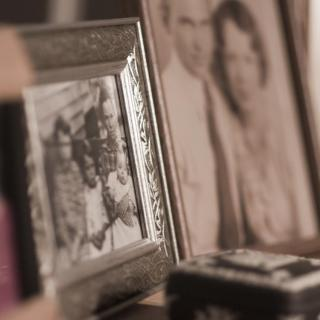 A line of framed family photos, all on a surface, some out of focus