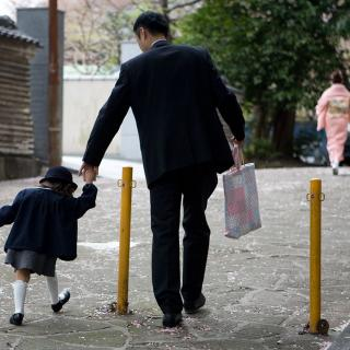 From behind, a Japanese man in a suit holds the hand of a small girl in a school uniform as they walk to school.