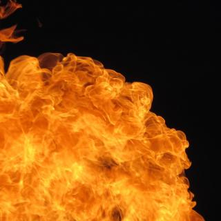 A billow of bright orange fire against a black background.