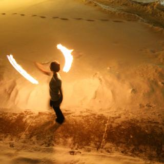 "Seen from above, in light cast only by flames, a solitary person swings two ""poi"" fire weights on chains (sometimes called ""fire juggling"")"