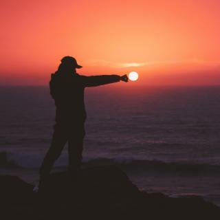 Against a brilliant sunset, a person in silhouette appears to punch the sun.