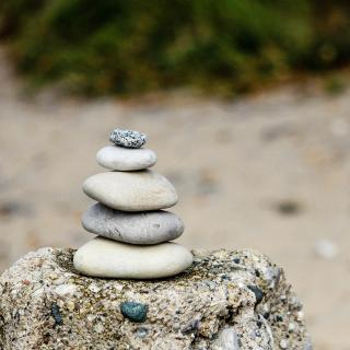 A stack of five stones on top of a larger rock.
