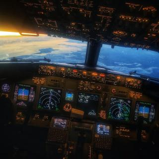 the view from a plane's cockpit, with instruments lit up and a view of terrain and a rising sun through the cockpit window