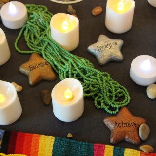 Candles, rocks, fabric and beads are seen in an up-close picture of an altar.