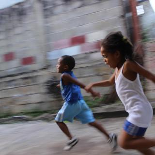 Two black children run, blurred, in joy and freedom down the street.