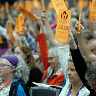 Delegates hold bright orange voting cards aloft to vote in General Session