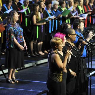 Musicians and choir perform, dressed colorfully for UU worship.