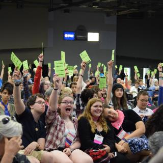 Youth delegates at the 2016 General Assembly (GA) holding up their cards to vote.