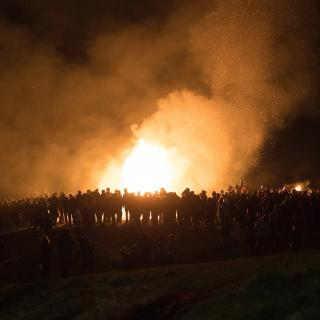A large number of people are in silhouette against the blaze of a bonfire