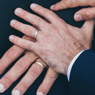 Two men's left hands, each with a wedding band, stacked lovingly.