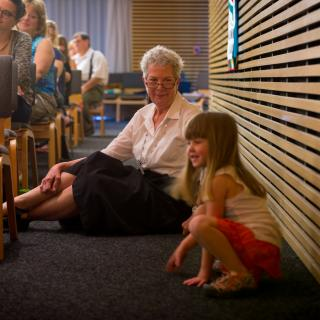 Older woman and small girl sit on the floor during worship at Unitarian Fellowship of Lawrence, Kansas.