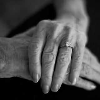 a black-and-white photo of a woman's wrinkled, graceful hands stacked on top of each other.