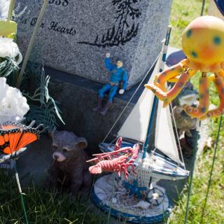 The corner of a gravestone, which is bedecked with toys and flowers and a fake butterfly stuck in the grass.