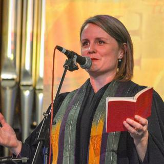 Rev. Gretchen Haley, in robe and stole, preaching on a church chancel.