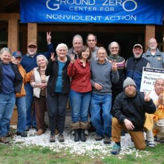 "A group of people stands in front of a banner reading ""Ground Zero Center for Nonviolent Action"""