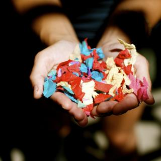 A person cups their hands to hold multi-colored confetti