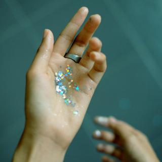 In an outstretched palm, star-shaped glitter sparkles