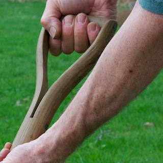a person's hands grasp the handle of a shovel, a green lawn in the background
