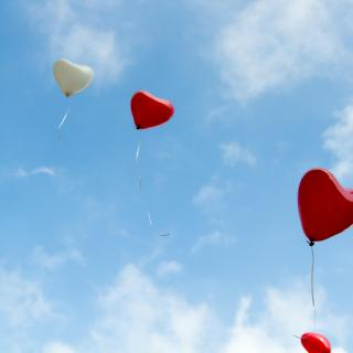 Red helium heart-shaped balloons float into a blue sky