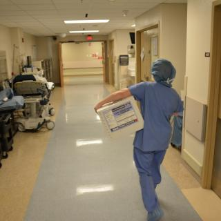 In a hospital corridor, a nurse in scrubs carries a cooler designated to hold donated organs.