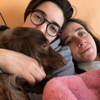 Two queers and a dachshund at home under a blanket
