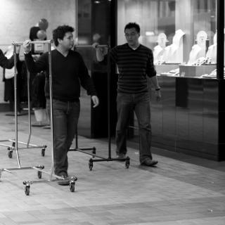 a trio of men wheel empty garment racks past a storefront