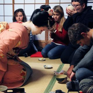 A kneeling Geisha and a white male in western clothing bow to each other in a tea ceremony, as westerners drink tea in the background.