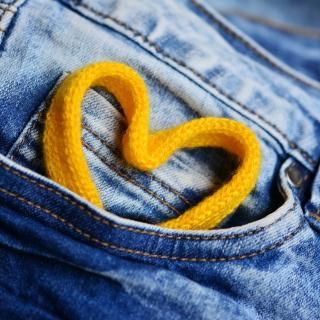 A yellow heart tucked in the front pocket of jeans