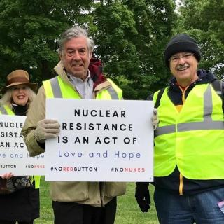 "Jonathan King and Jerry Ross at a recent nuclear weapons protest holding a sign that says ""Nuclear Resistance is an Act of Love and Hope #NoRedButton #NoNukes"""