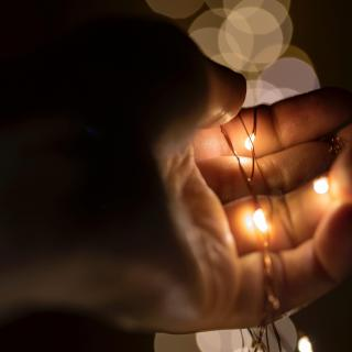 A hand holding a string of small lights