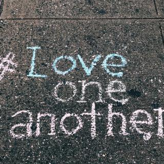 On pavement, the message written in pastel chalk, (hashtag) love one another.