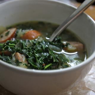 a bowl full of kale soup, spoon sticking out