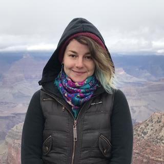 Katie Gelfand, in a scarf and hoodie, in front of the Grand Canyon