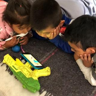 Shelter children watching cartoons on a smart phone which is propped up on a plastic toy gun