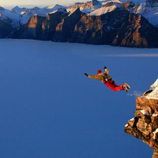 Person leaping off a ledge with snow in the mountains