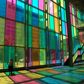 Sunlight shines through multicolored rectangular windows casting colorful shadows on the floor.