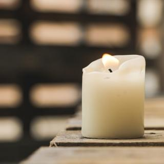 A white pillar candle, lit, with patterns of light and shadow in the background.