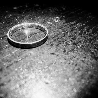 a black-and-white photo of a wedding band on a table