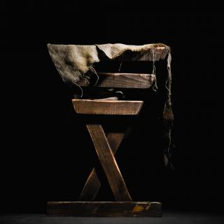 In stark light, against a black background, a simple wooden manger
