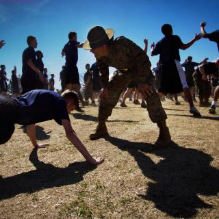 Amidst a field of men doing jumping jacks, a drill instructor in uniform bends over to shout at a man doing push-ups.