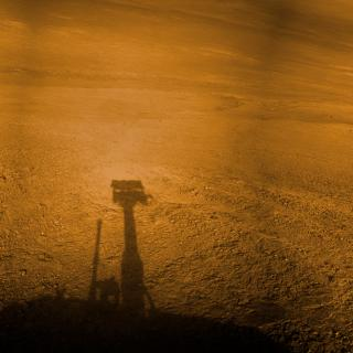 Against the red, dusty surface of Mars, the silhouette of the Mars Rover Opportunity appears as a little robot head.