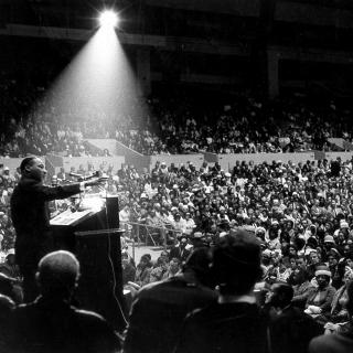 Martin Luther King, Jr. speaking to a crowd in San Francisco on June 30, 1964. In this black-and-white photograph, the humidity of the evening has cause a beam of light to appear surrounding King, as he gestures from a lectern.