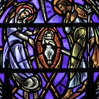 Stained glass detail from the Dominican church of St Vincent Ferrer in New York, showing Jesus in a manger surrounded by Mary and Joseph.