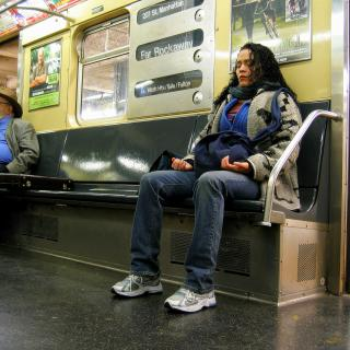 On a NYC subway car, a woman sits with both feet planted on the floor, hands held lightly in meditation position, with her eyes closed.
