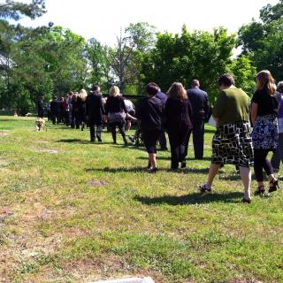A group of mourners walks across a cemetery green.